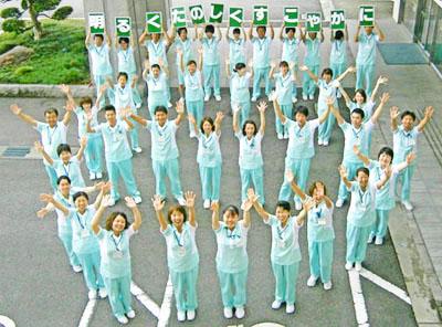 ロゴマーク「母」の人文字を職員数十名がみどり苑玄関先で描いる様子の写真